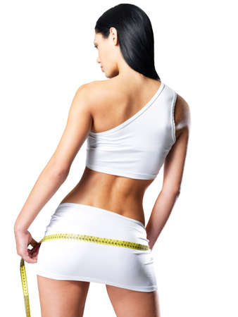 Rear view of sporty woman with slim body measuring hips - model posing in studio Stock Photo