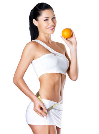 Smiling girl measures figure with a measuring tape and holding the orange. Healthy lifestyle cocnept.