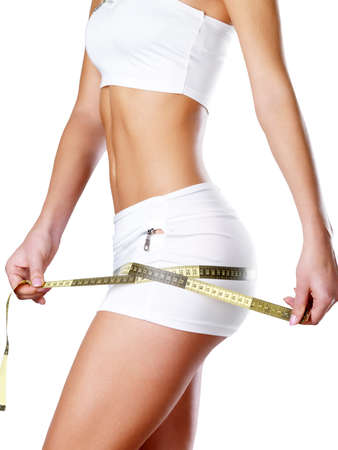 female body: Beautiful feamle body with measuring tape. Healthy lifestyle cocnept. Stock Photo