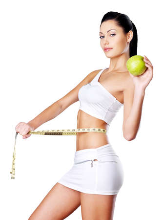 Slimming woman measures figure with a measuring tape and holding the apple. Healthy lifestyle cocnept. photo