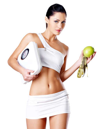 Healthy woman stands with the scales and green apple. Healthy eating concept. photo