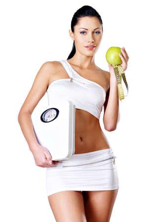 manzana: Mujer sana de pie con las escalas y la manzana verde. Alimentaci?n saludable concepto.
