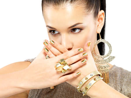 Pretty woman with golden nails and beautiful gold jewelry isolated on white background Stock Photo - 21886384
