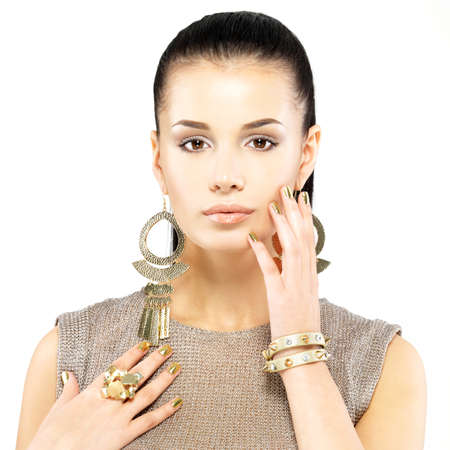 Pretty woman with golden nails and beautiful gold jewelry isolated on white background Stock Photo - 21886387