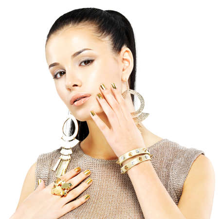 Pretty woman with golden nails and beautiful gold jewelry isolated on white background Stock Photo - 21886388