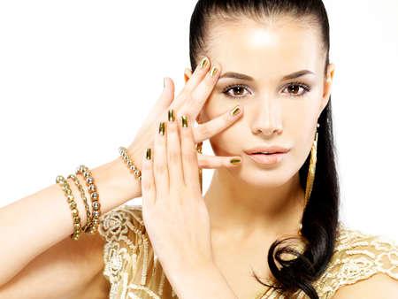 stílus: Csinos nő arany körmök és gyönyörű arany ékszerek, elszigetelt, fehér, háttér