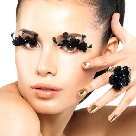 Closeup portrait of the beautiful woman with long black false eyelashes makeup and golden nails.  isolated on white background photo
