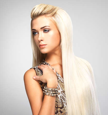 Mooie vrouw met lang recht blond haar. Fashion model poseren in de studio.