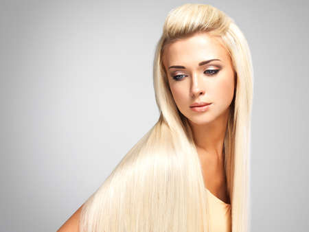 gray hair: Beautiful woman with long straight blond hair. Fashion model posing at studio.