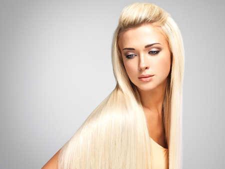 cabello lacio: Mujer hermosa con el pelo largo y rubio recta. Moda modelo posando en el estudio. Foto de archivo