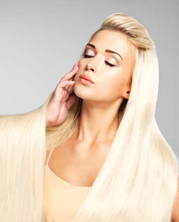 long straight hair: Beautiful woman with long straight blond hair. Fashion model posing at studio.