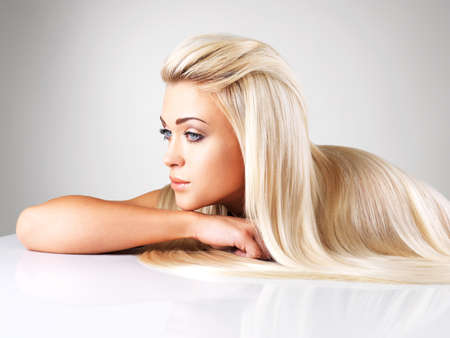 grey hair female: Beautiful woman with long straight blond hair. Fashion model posing at studio.