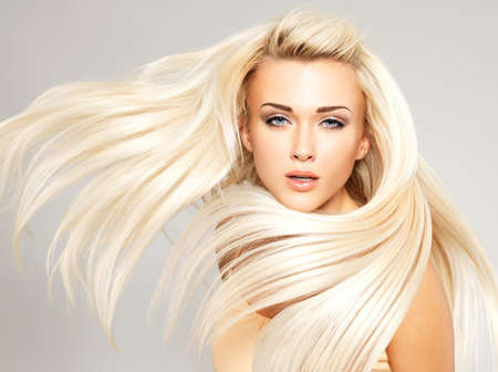 capelli lunghi: Bella donna con lunghi capelli biondi dritti. Modella in posa nello studio. Archivio Fotografico