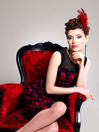 Beautiful adult woman with fashion hairstyle and red armchair poses at studio photo