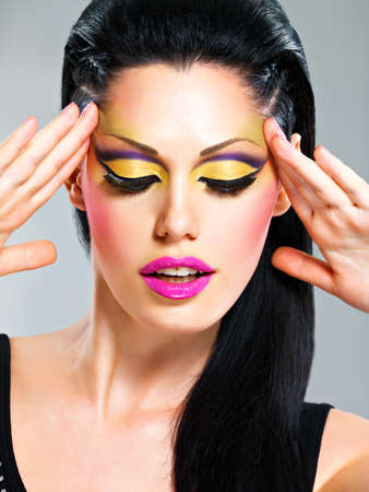 Beauty  woman with fashion makeup on  face poses at studio photo