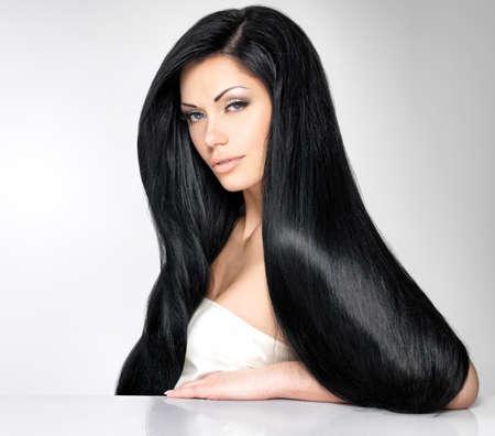 긴 직선 머리를 가진 아름 다운 갈색 머리 여자의 초상화는 회색 배경에 포즈