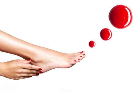 pedicura: Hermosos pies femeninos con pedicure rojo y gotas de esmalte de uñas sobre fondo blanco