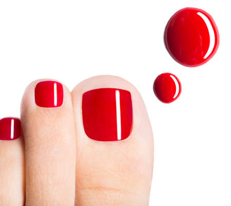 polish: Beautiful female toes with red pedicure and drops of nail polish  over white background