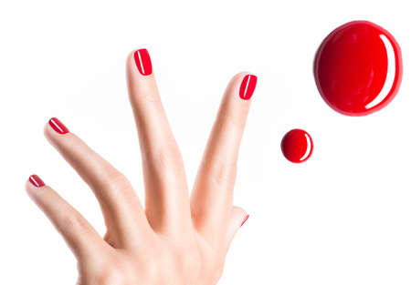 Beautiful female hands with red manicure and  drops of nail polish   Stock Photo