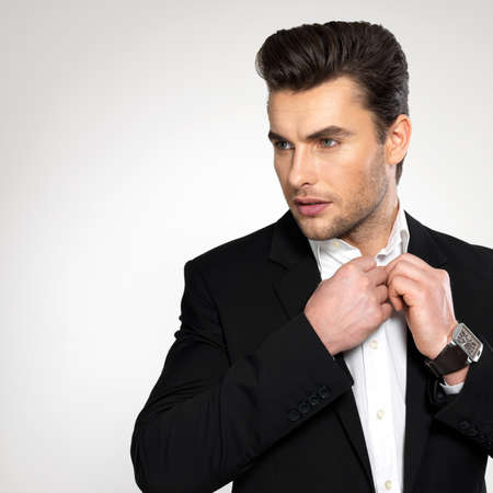 Fashion young businessman black suit casual  poses at studio Stock Photo - 22059516