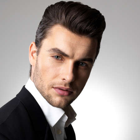 men hairstyle: Fashion young businessman black suit casual  poses at studio