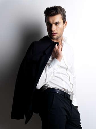 白いシャツのファッション若い男コントラスト影と壁を越えて黒いジャケットを保持します。 写真素材