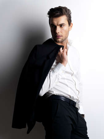 Fashion jonge man in wit overhemd houdt de zwarte jas over muur met contrast schaduwen Stockfoto - 22059490