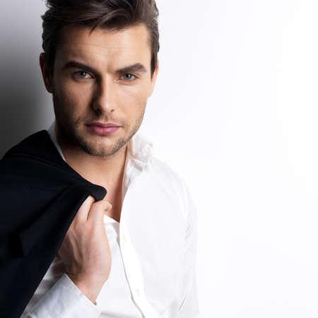 Fashion jonge man in wit overhemd houdt de zwarte jas over muur met contrast schaduwen