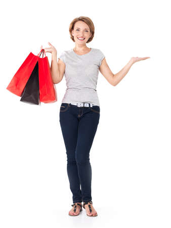 Happy white woman with shopping bags over white background - full portrait photo