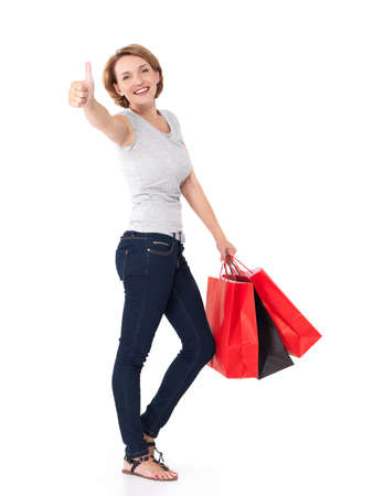 Portrait of a beautiful adult happy woman with thumbs up sign after shopping over white background photo