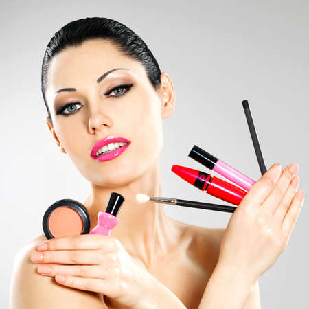 Beautiful woman with makeup cosmetic tools near her face. Stock Photo - 22132257