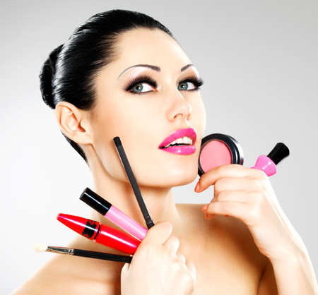 Beautiful woman with makeup cosmetic tools near her face.  Stock Photo - 22132263