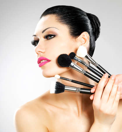 Beautiful woman with makeup brushes near her face. Pretty girl poses at studio with cosmetic tools Stock Photo - 22132261
