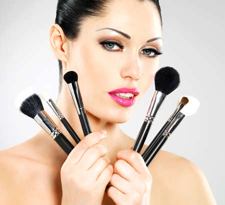 Beautiful woman with makeup brushes near her face. Pretty girl poses at studio with cosmetic tools Stock Photo - 22132260