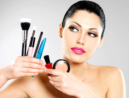 Beautiful woman with makeup brushes near her face. Pretty girl poses at studio with cosmetic tools Stock Photo - 22132265