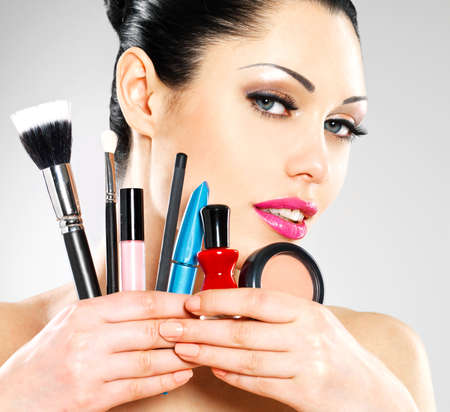 Beautiful woman with makeup brushes near her face. Pretty girl poses at studio with cosmetic tools photo