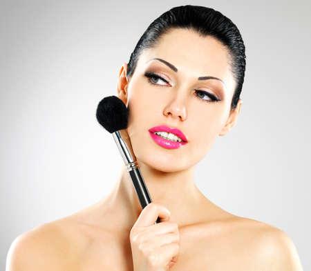 Portrait of  beautiful woman applying blusher on face using cosmetic brush Stock Photo - 22132267