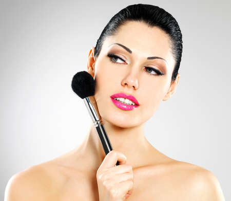 Portrait of  beautiful woman applying blusher on face using cosmetic brush Stock Photo - 22132267