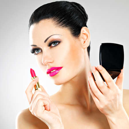 Beautiful woman makes makeup applying pink lipstick on lips.  Stock Photo - 22132262