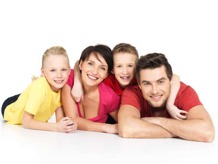 Portrait of the happy young family with two children lying at studio on white floor Stock Photo - 22059524