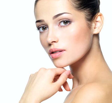 cute: Volto di giovane donna di bellezza. Concetto di cura della pelle. Ritratto del primo piano isolato su bianco.