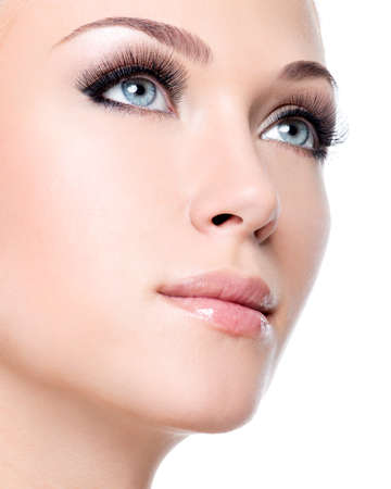 ojo: Primer retrato de la joven y bella mujer blanca con largas pestañas falsas sobre el fondo blanco