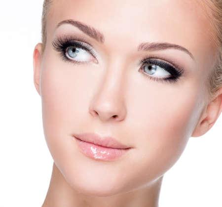 false eyelash: Closeup portrait of young beautiful white woman with long false eyelashes  over white background
