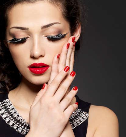 eyelashes: Fashion woman with modern creative makeup using false eyelashes red manicure