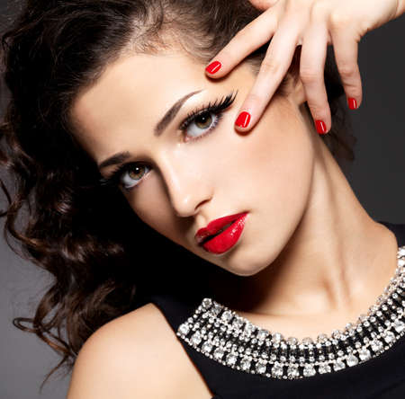 finger on lips: Beauty fashion woman with red nails, lips and golden eye makeup  - on black background