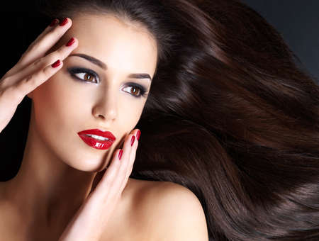 Schöne Frau mit langen braunen geraden Haaren und roten Nägeln liegen auf dem dunklen Hintergrund