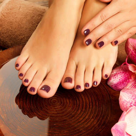 nails manicure: Closeup photo of a female feet at spa salon on pedicure procedure. Female legs in water decoration  the flowers.