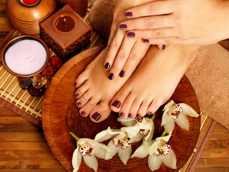 manos y pies: Primer foto de un pies femeninos en sal?n del balneario sobre el procedimiento de pedicura. Piernas femeninas en decoraci?n regar las flores.