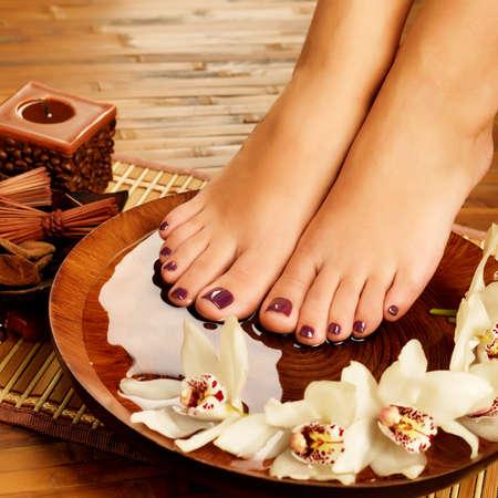 foot massage: Closeup photo of a female feet at spa salon on pedicure procedure. Legs care concept
