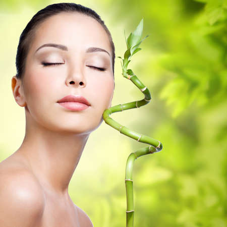 Closeup healthy face of young woman with sprout in hands over nature green background photo